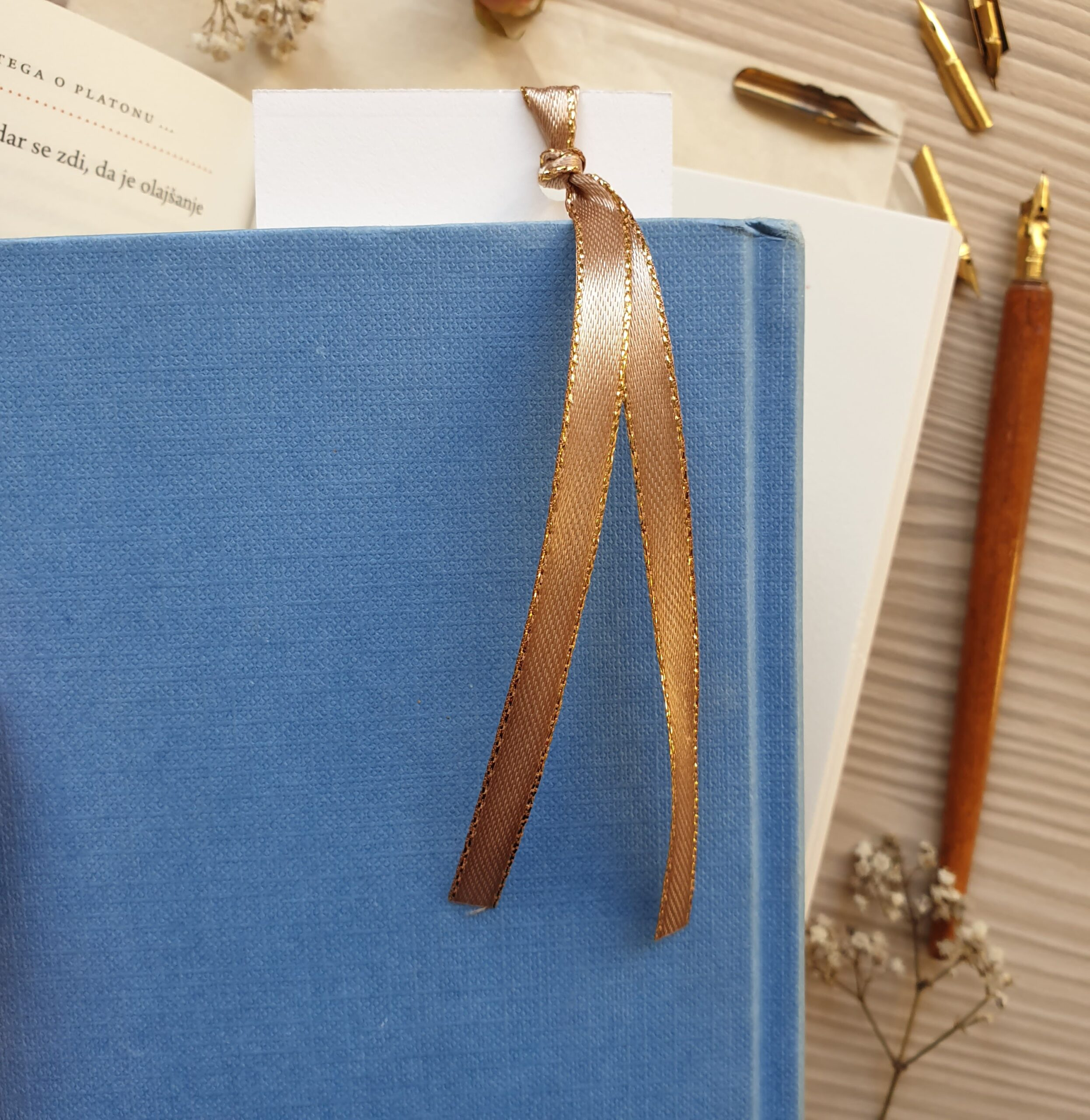 Floral bookmark in a book, gold